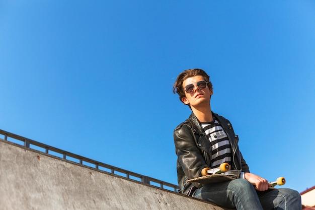 Junger mann mit seinem skateboardfahren am rochenpark
