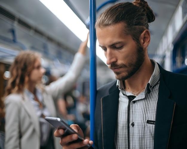 Junger mann mit seinem smartphone in einer u-bahn