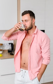 Junger mann mit seiner hand in seiner tasche einen kaffee genießend