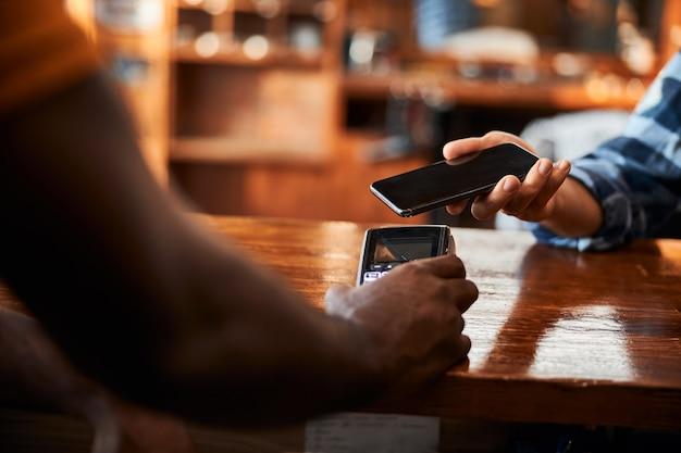 Junger mann mit smartphone für kontaktloses bezahlen