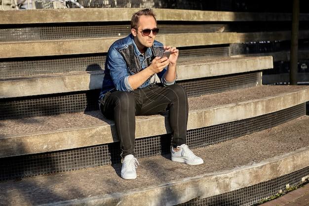 Junger mann mit smartphone in den händen sitzt auf der treppe und sendet nachrichten mit seinem telefon.