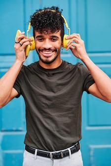 Junger mann mit smartphone und kopfhörer im freien vor einer tür