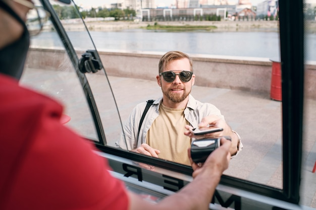 Junger mann mit sonnenbrille bezahlt für fast food durch kontaktloses zahlungssystem