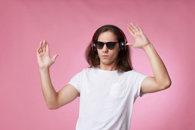 Junger mann mit sonnenbrille hört musik mit kopfhörern und tanzt auf rosa hintergrund