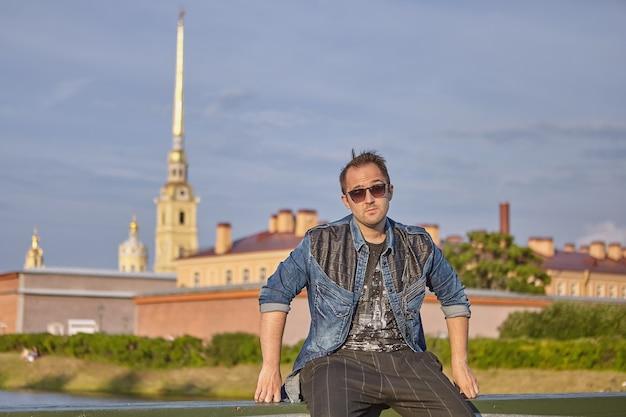Junger mann mit sonnenbrille reist über st. petersburg, russland.