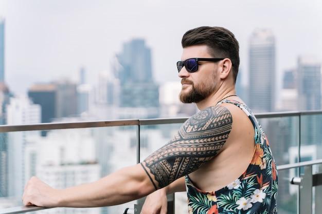 Junger mann mit sonnenbrille und ärmellosem hemd mit blick auf die stadt