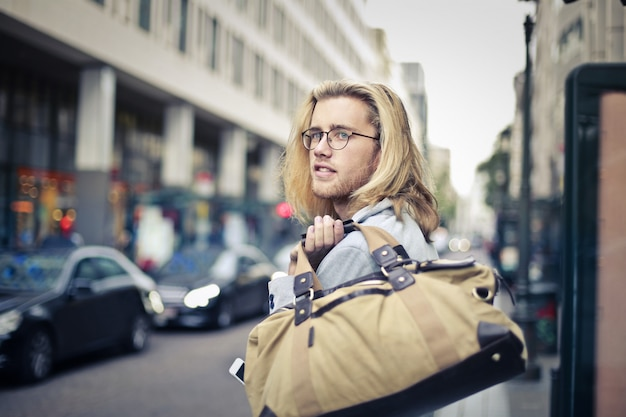 Junger mann mit sporttasche in der stadt
