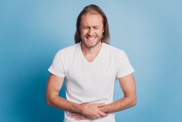 Junger mann mit starken magenschmerzen berührt handbauch isoliert