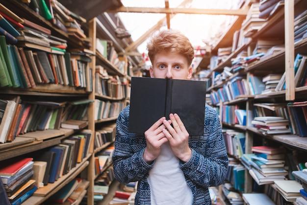 Junger mann mit staunenden augen steht in einer gemütlichen öffentlichen bibliothek und bedeckt seinen mund mit einem schwarzen buch.