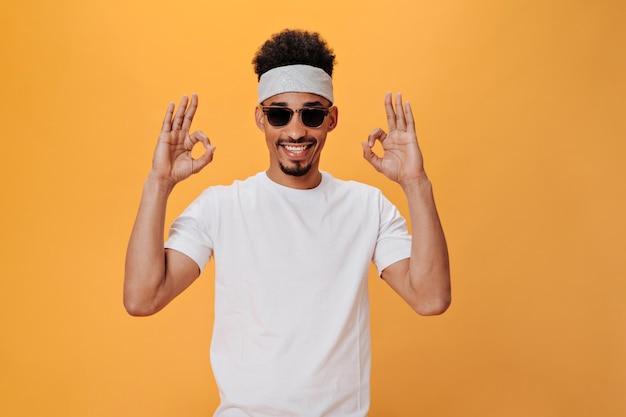 Junger mann mit stirnband und stilvoller brille zeigt zeichen ok
