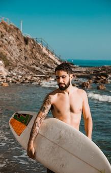 Junger mann mit surfbrett am strand in der nähe von wasser