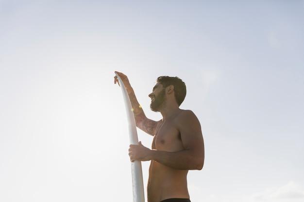 Junger mann mit surfbrett gegen klaren himmel