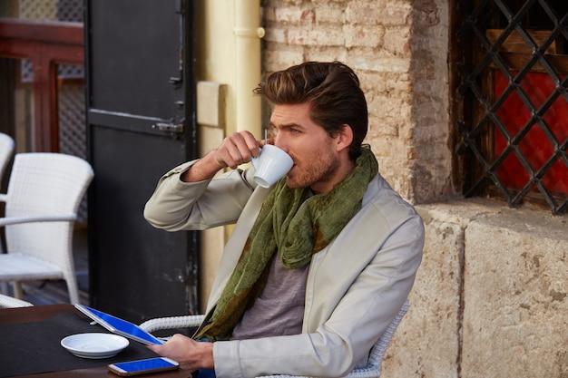 Junger mann mit tabletten-pc-note in einem café