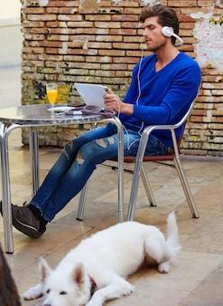 Junger mann mit tabletten-pc-note mit hund