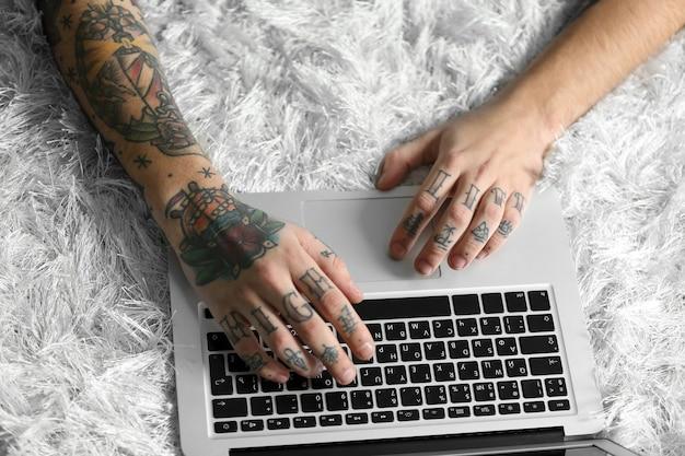 Junger mann mit tätowierung unter verwendung des laptops auf einem boden zu hause