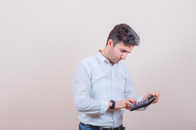 Junger mann mit taschenrechner in weißem hemd, jeans und beschäftigt aussehend