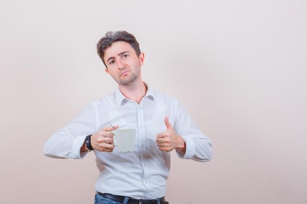 Junger mann mit tasse getränk, daumen nach oben in weißem hemd, jeans zeigend