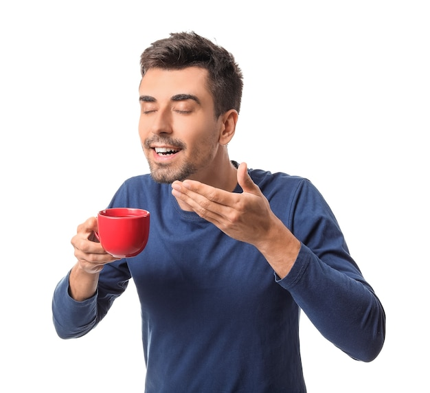 Junger mann mit tasse heißem kaffee auf weißem hintergrund
