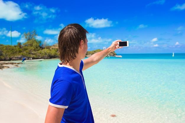 Junger mann mit telefon am tropischen karibischen strand