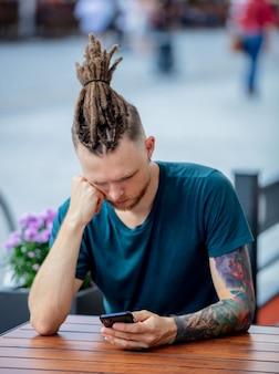 Junger mann mit telefon sitzt am tisch in einem café in der stadt