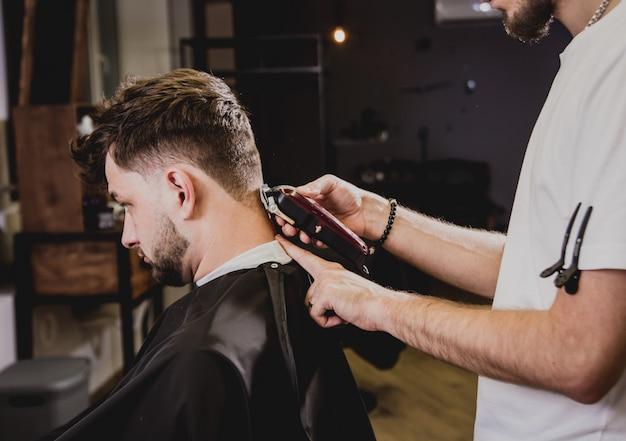 Junger mann mit trendigem haarschnitt am friseurladen. barber macht die frisur und bart schneiden.