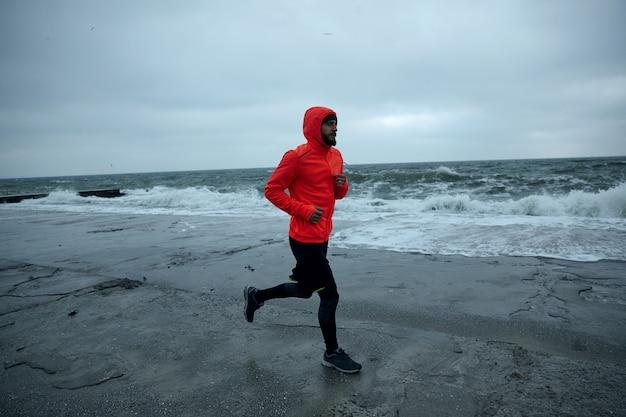 Junger mann mit üppigem barttraining am strand am kalten frühen morgen, der schwarze sportliche kleidung und warmen orange mantel mit kapuze beim joggen trägt. fitness- und sportkonzept