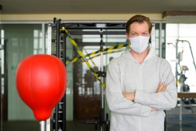 Junger mann mit verschränkten armen trägt maske und bereit zum boxen im fitnessstudio