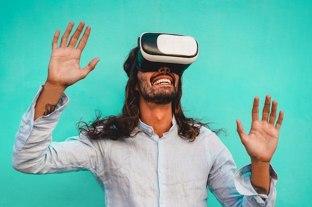 Junger mann mit virtual-reality-headset mit blauer wand im hintergrund - trendiger typ, der spaß mit neuer trendtechnologie hat - technologie, spaß und zukunftskonzept - fokus auf männlichem mund und vr brille