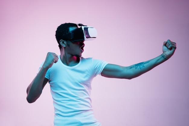 Junger mann mit vr-brille im neonlicht