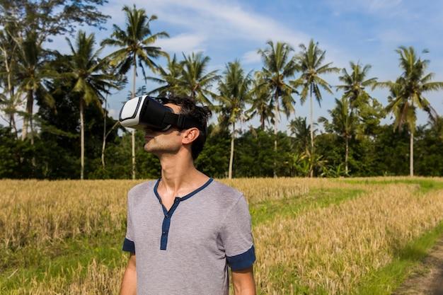 Junger mann mit vr-gläsern auf dem tropischen reisgebiet