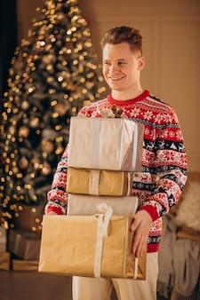 Junger mann mit weihnachtsgeschenken