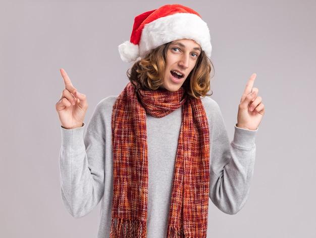 Junger mann mit weihnachtsmütze mit warmem schal um den hals glücklich und überrascht, der mit den zeigefingern auf die weiße wand zeigt