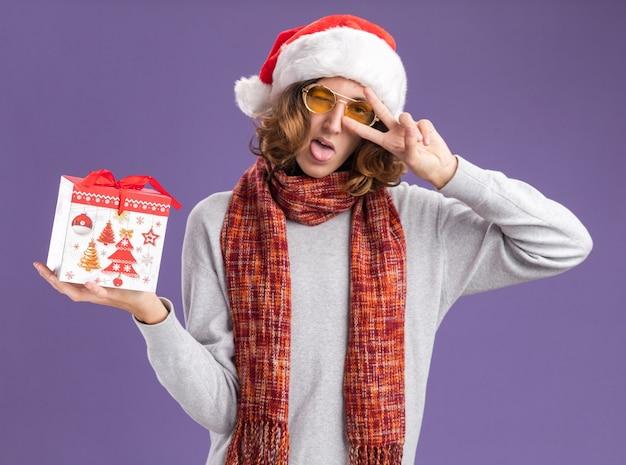 Junger mann mit weihnachtsmütze und gelber brille mit warmem schal um den hals, der ein weihnachtsgeschenk hält, das ein v-zeichen zeigt, das über der lila wand steht