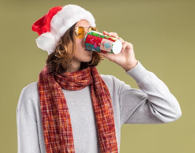 Junger mann mit weihnachtsmütze und gelber brille mit warmem schal um den hals, der saft aus bunten pappbechern trinkt, die über grüner wand stehen