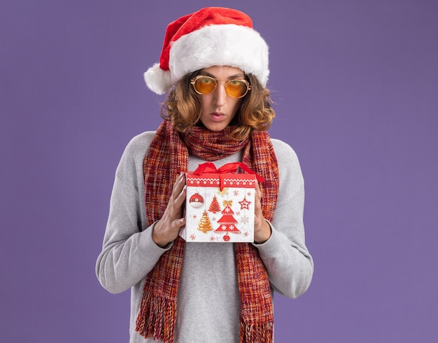 Junger mann mit weihnachtsmütze und gelber brille mit warmem schal um den hals, der weihnachtsgeschenk besorgt über lila wand hält