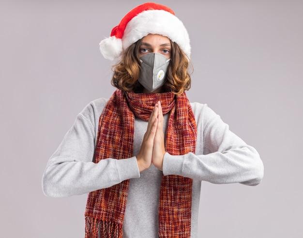 Junger mann mit weihnachtsmütze und gesichtsschutzmaske mit warmem schal um den hals, der hände zusammen mit ernstem gesicht über weißer wand hält