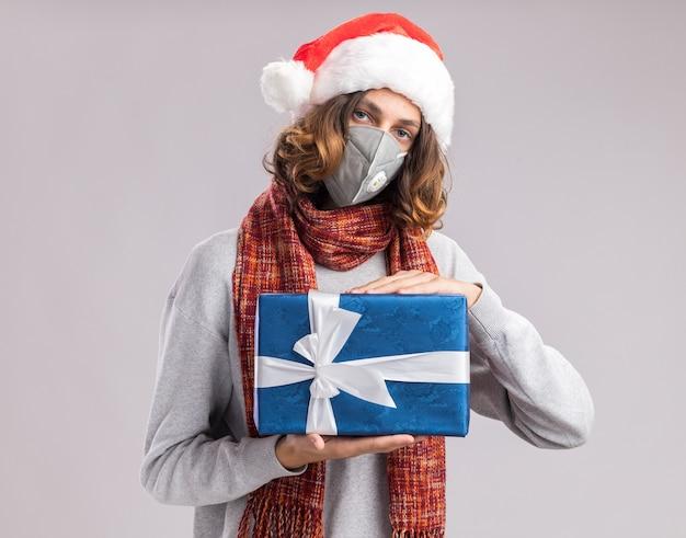 Junger mann mit weihnachtsmütze und gesichtsschutzmaske mit warmem schal um den hals, der weihnachtsgeschenk mit ernstem gesicht über weißer wand hält