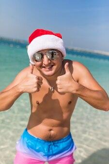 Junger mann mit weihnachtsmütze und sonnenbrille zeigt daumen hoch, während er im meeresraum steht
