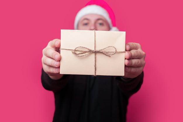 Junger mann mit weihnachtsmütze zeigt ein geschenk, während er etwas auf roter wand annonciert