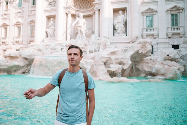 Junger mann nahe brunnen fontana di trevi mit münzen in den händen