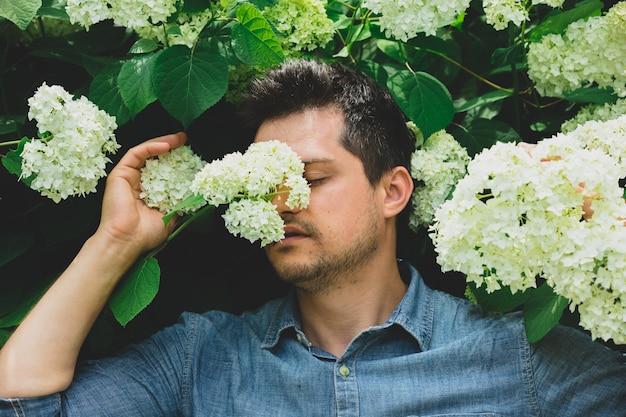 Junger mann nahe busch der weißen blumen in einem garten