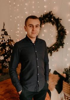 Junger mann nahe einem eleganten weihnachtsbaum. weihnachtsmorgen. neujahrsausstattung. valentinstag feier