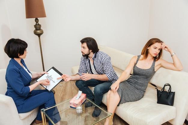 Junger mann nimmt mit doktor. therapeut hält eine handzeichnung und betrachtet kerl. junge frau ist verzweifelt. sie schaut nach rechts