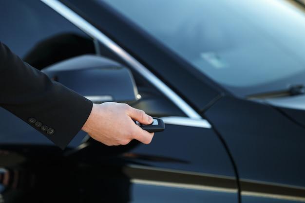 Junger mann öffnet seine autotür mit dem fernbedienungsschlüssel