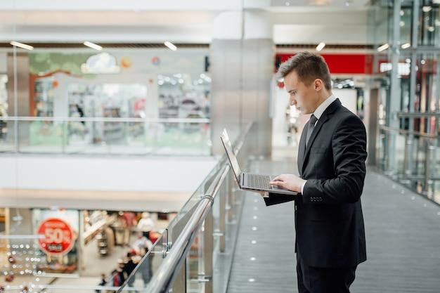 Junger mann, ökonom, kommunizieren mit dem laptop, arbeiten, lernen, im business center, profilansicht