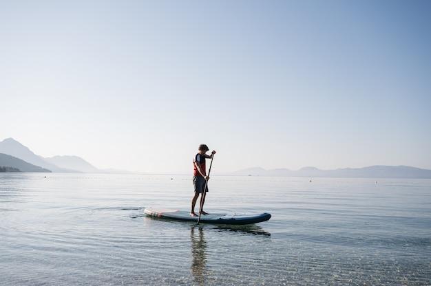 Junger mann paddelt an bord
