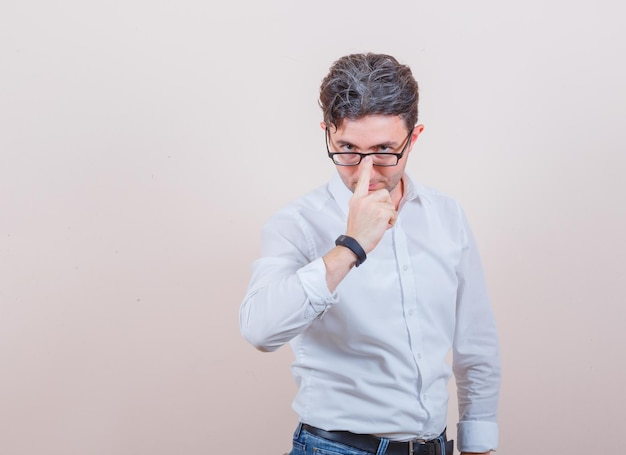 Junger mann passt seine brille in weißem hemd, jeans und sieht ernst aus
