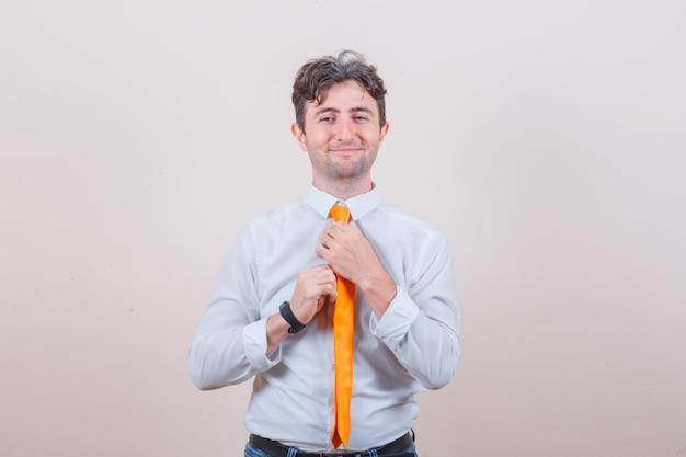 Junger mann passt seine krawatte in hemd, jeans und sieht glücklich aus