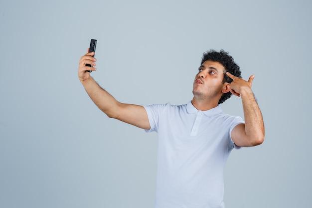 Junger mann posiert beim selfie auf dem handy im weißen t-shirt und sieht selbstbewusst aus, vorderansicht.