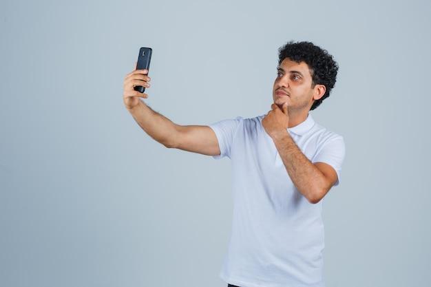Junger mann posiert beim selfie im weißen t-shirt und sieht süß aus. vorderansicht.